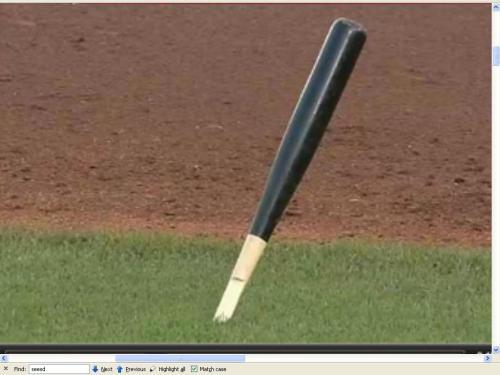 sharp end of broken bat stuck in ground